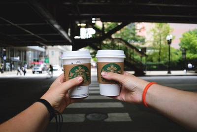 Two hands holding Starbucks cups toasting