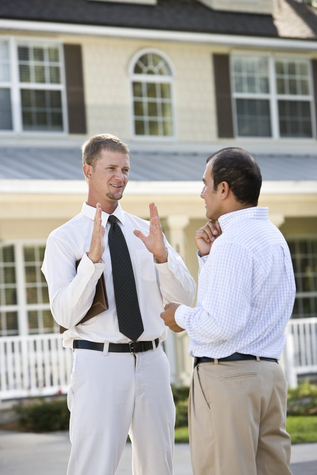 Two men talking in street outside house