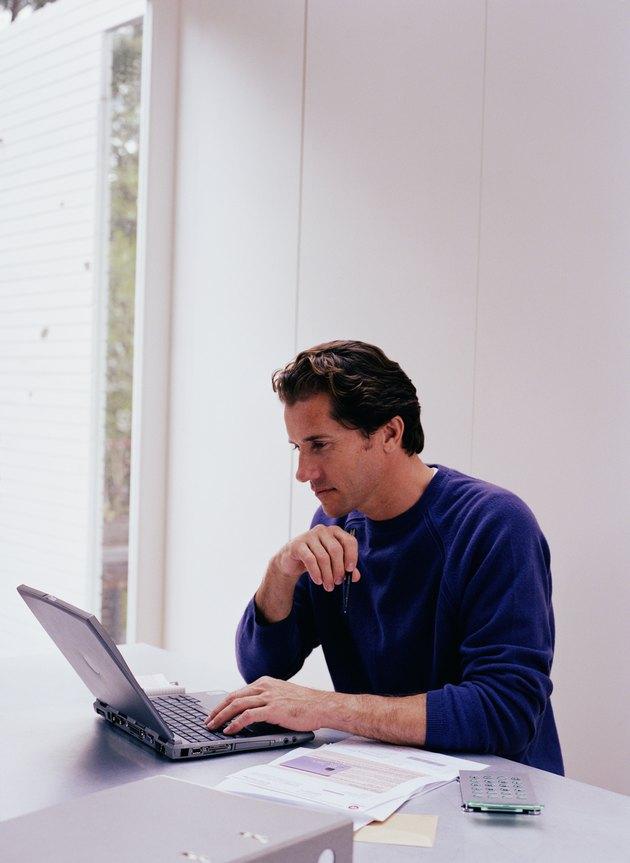 Mature man at table using laptop computer