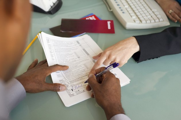 Man signing financial paperwork