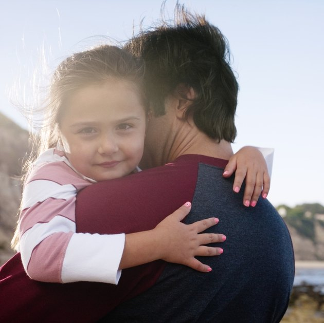 Daughter (6-7) and father hugging, girl looking at camera, outdoors