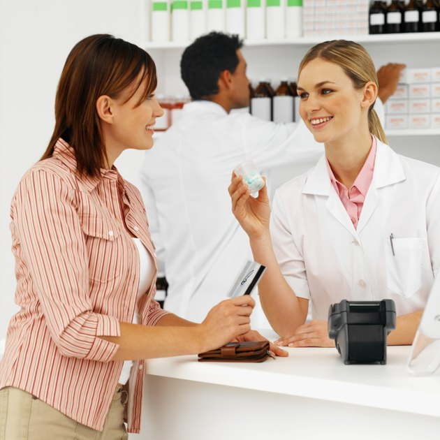 Close-up of female pharmacist showing container of tablets to patient with male pharmacist in background