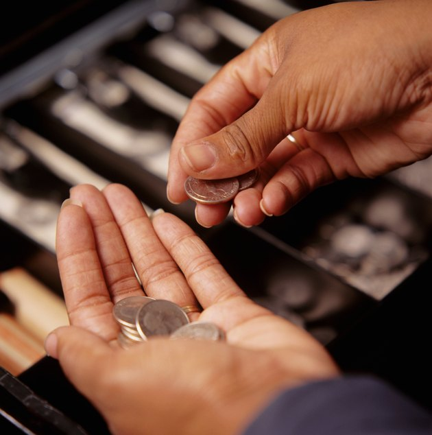 Teller counting coins at cash register, close-up, elevated view