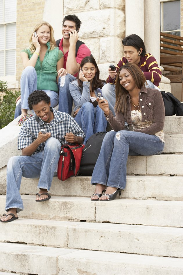 Group of young people sitting on stairs with mobile phones