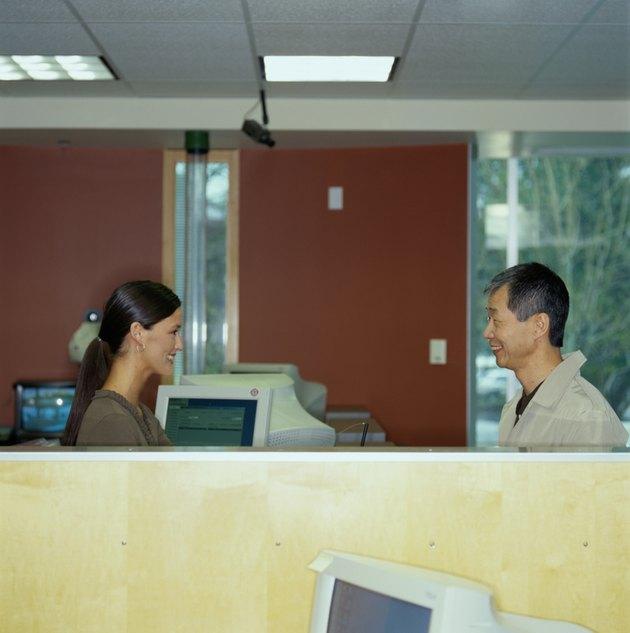 Young bank teller assisting senior customer, side view