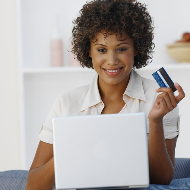 Front view of young woman holding credit card with laptop in front of her