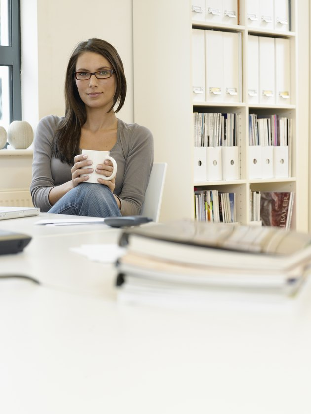 Woman at desk in office, holding mug, portrait