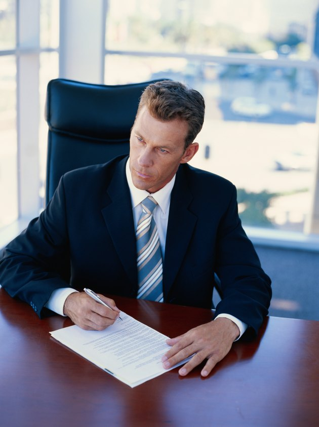 Businessman sitting in office signing document, looking away