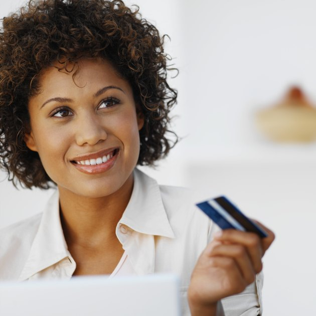 Portrait of a woman holding a credit card and using a laptop