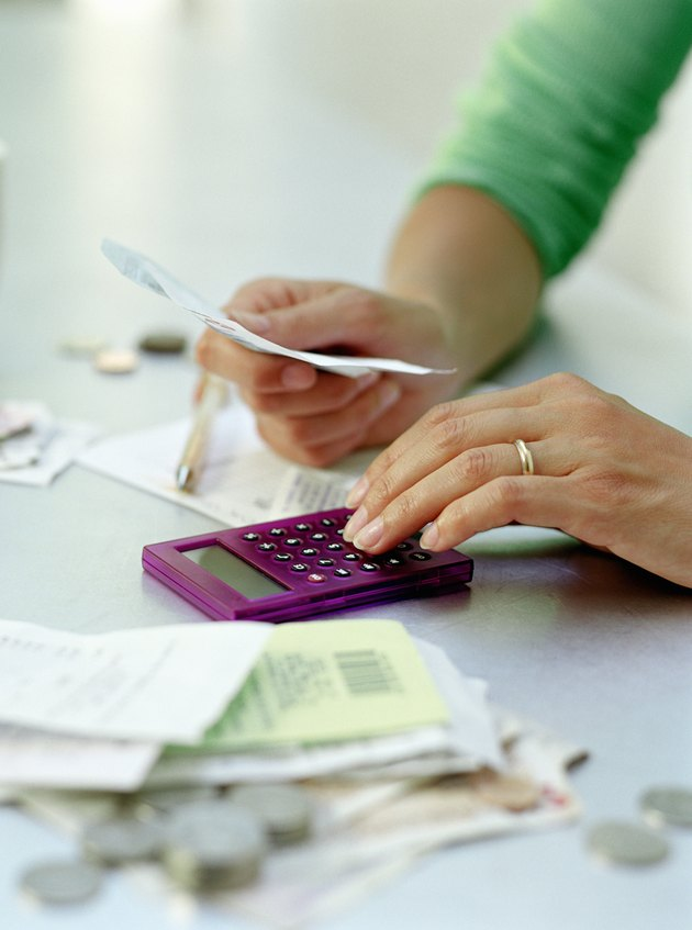 Woman reviewing receipts with calculator, close-up of hands
