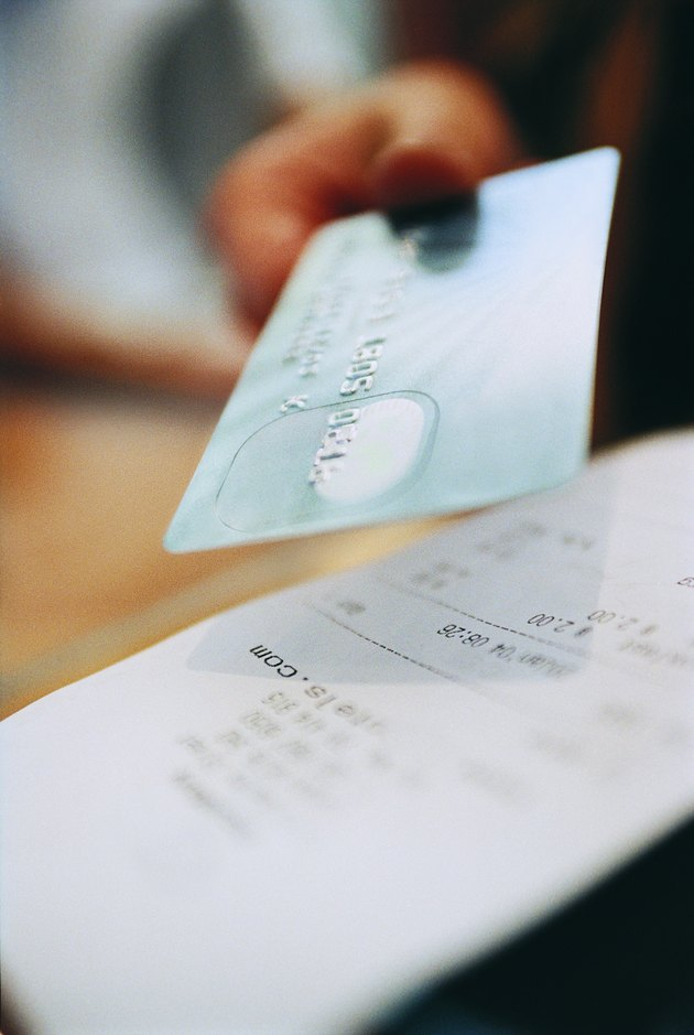 Receipt and a Person Paying With a Credit Card