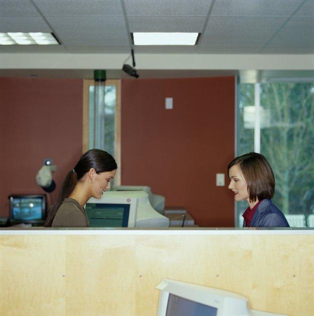 Bank teller assisting female customer, side view