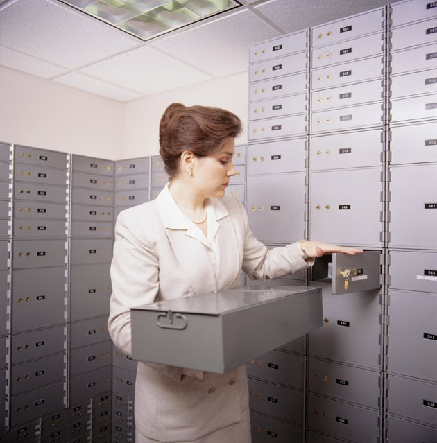 Woman opening safe box in bank