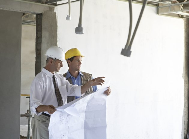 Two Men Standing in a Partially Constructed Room, Holding Blueprints