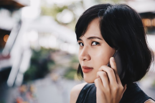 Asian woman looking skeptically at camera while talking on mobile phone