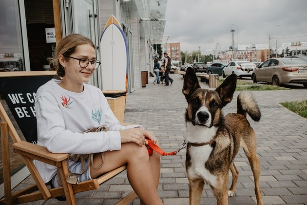 Young white woman seated with dog on sidewalk
