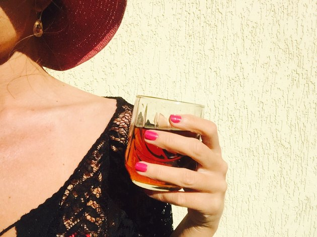 Woman with pink nail polish holding glass of whiskey