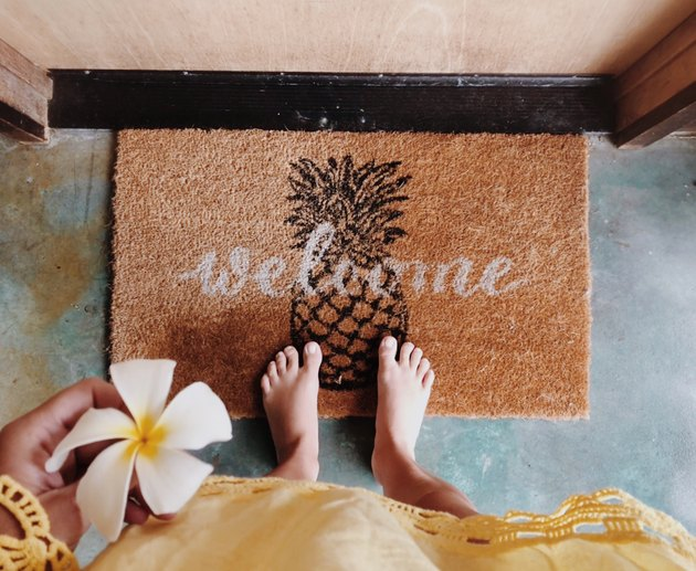 Welcome mat with pineapple and POV holding orchid
