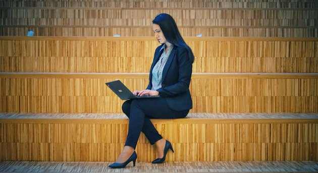 Woman in business casual on laptop on bamboo stairs