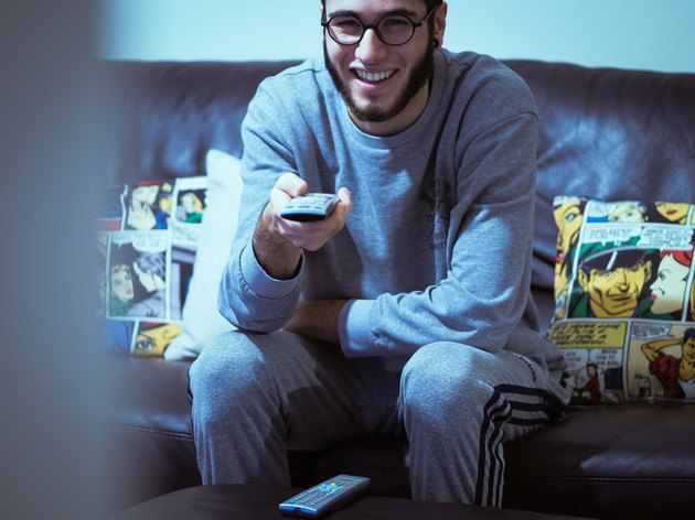 Young white man using remote control and smiling