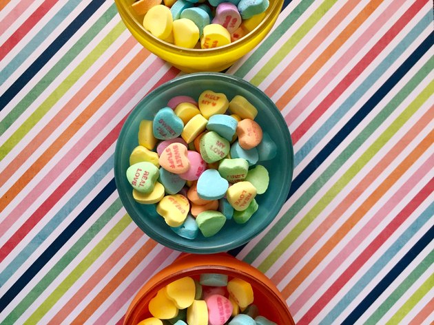 Conversation hearts in bowl against rainbow striped background