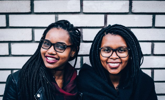 Two cute young Black women in glasses smiling together