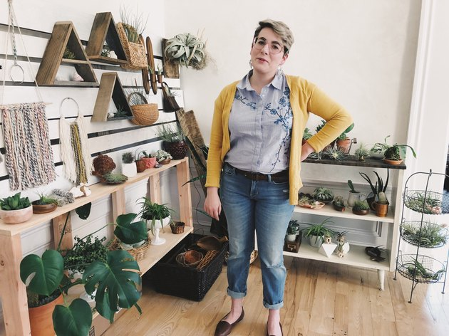 Woman in yellow cardigan stands in front of houseplants