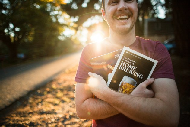White man holding a lot of home brewing books smiling in the sunset
