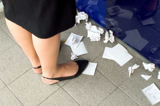 Woman standing at ATM surrounded by discarded receipts