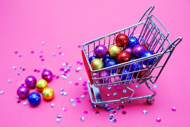 A shopping cart with candies on a pink background