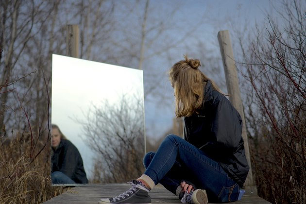 Young woman looks at mirror reflection in wooded field