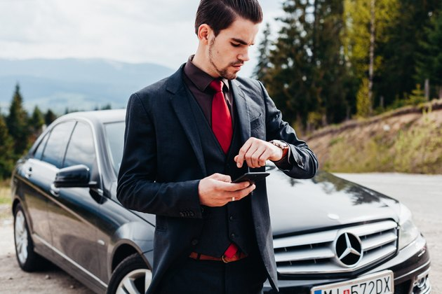 Stylish young man in suit poses in front of BMW