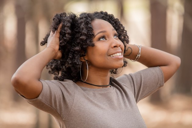 Young Black woman smiling in wooded area