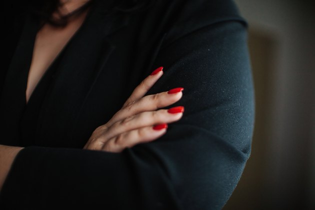 Closeup, businesswoman with folded arms and red nails