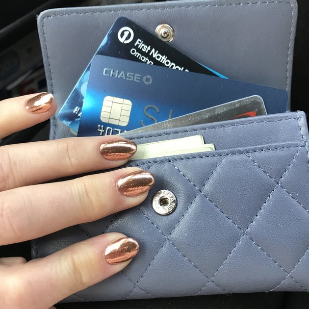 Woman's manicured fingers on top of wallet with credit cards