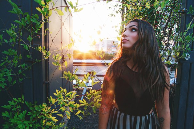Woman amid rooftop vines at golden hour
