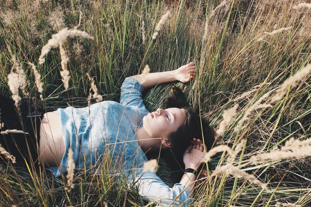 Woman in blue sweater lying in field