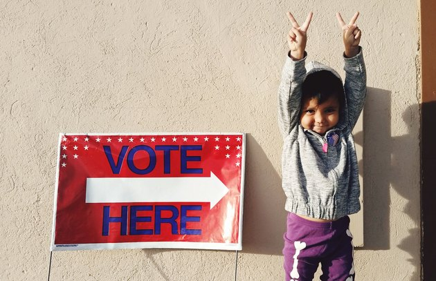 "Small child flashing peace signs next to ""Vote Here"" sign"