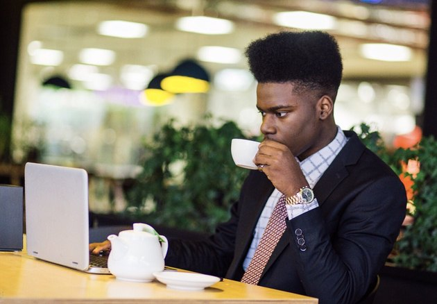 Young Black man in business suit drinking tea at laptop