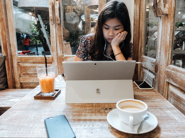 Woman in coffee shop using tablet/laptop