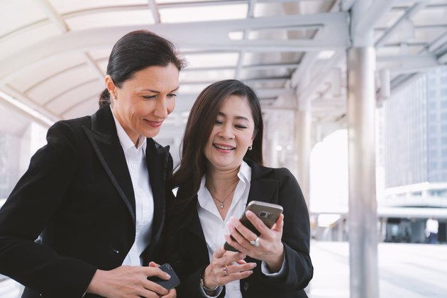 Two senior businesswomen meeting and using smartphone at modern building