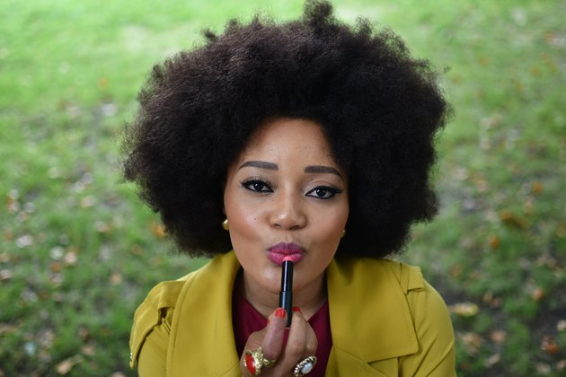 Portrait of Black woman with Afro applying lipstick