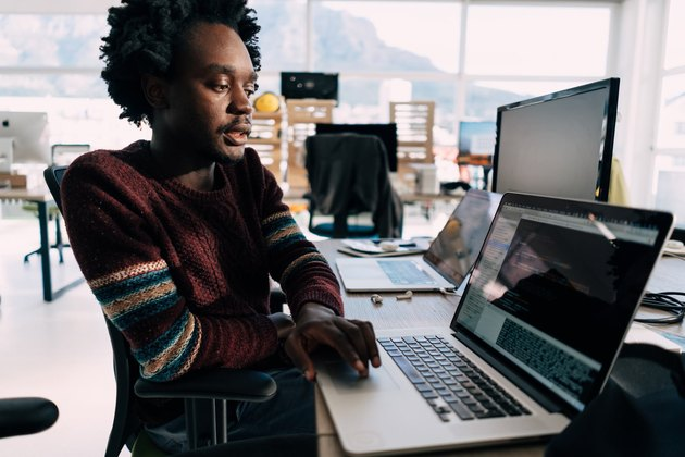 Black man with laptop at computer station in bright office