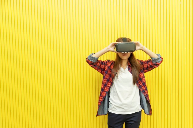 Young woman using VR headset against yellow wall