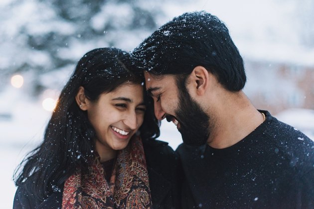 South Asian couple cuddling in the snow