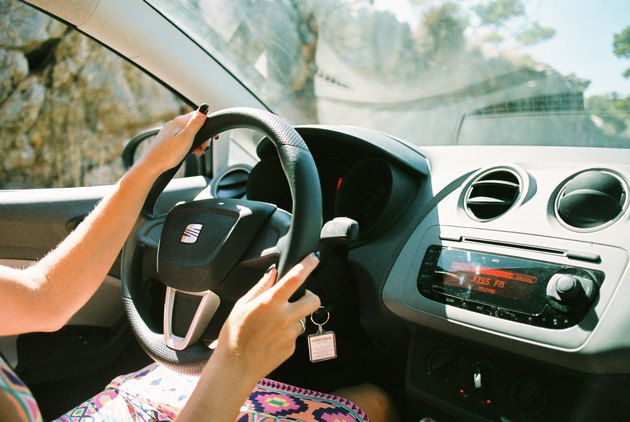 Woman's hands on steering wheel of sunny car