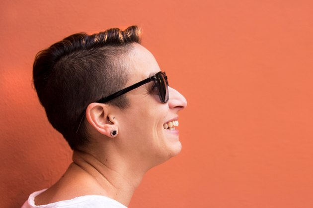 Woman with buzzcut smiling against orange wall