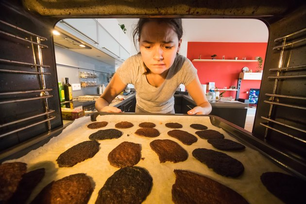 Woman grimaces at burnt cookies in the oven