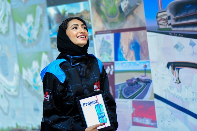 Beaming hijabi surrounded by project posters on water use