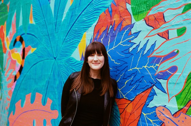 Woman in black poses in front of colorful mural of leaves